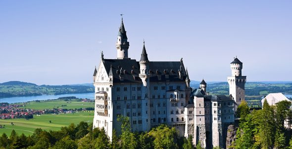 Castle Neuschwanstein stands glowing above the lake