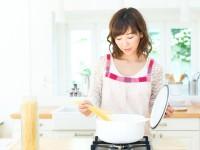 鍋で調理をする女性