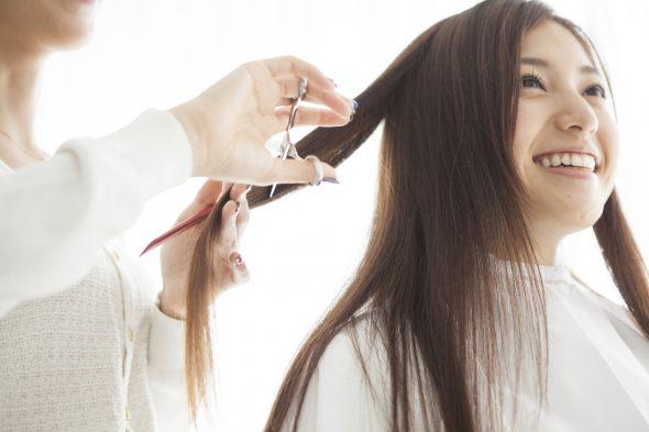 美容室でロングヘアをカットする女性