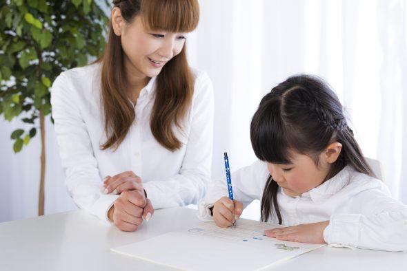 母親に勉強を教えてもらう女の子