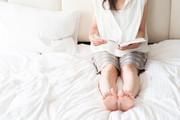 ベッドの上でBL漫画を読む女性
